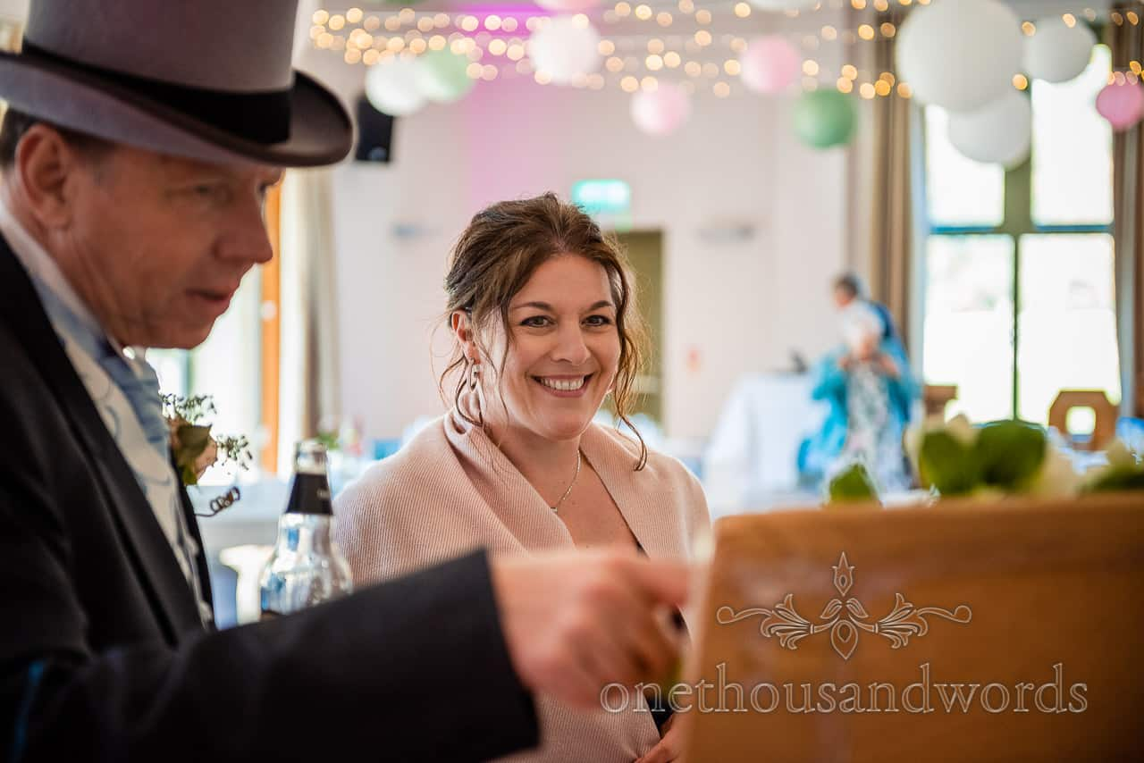 Happy female wedding guest smiles as wedding guest in top hat points at table plan