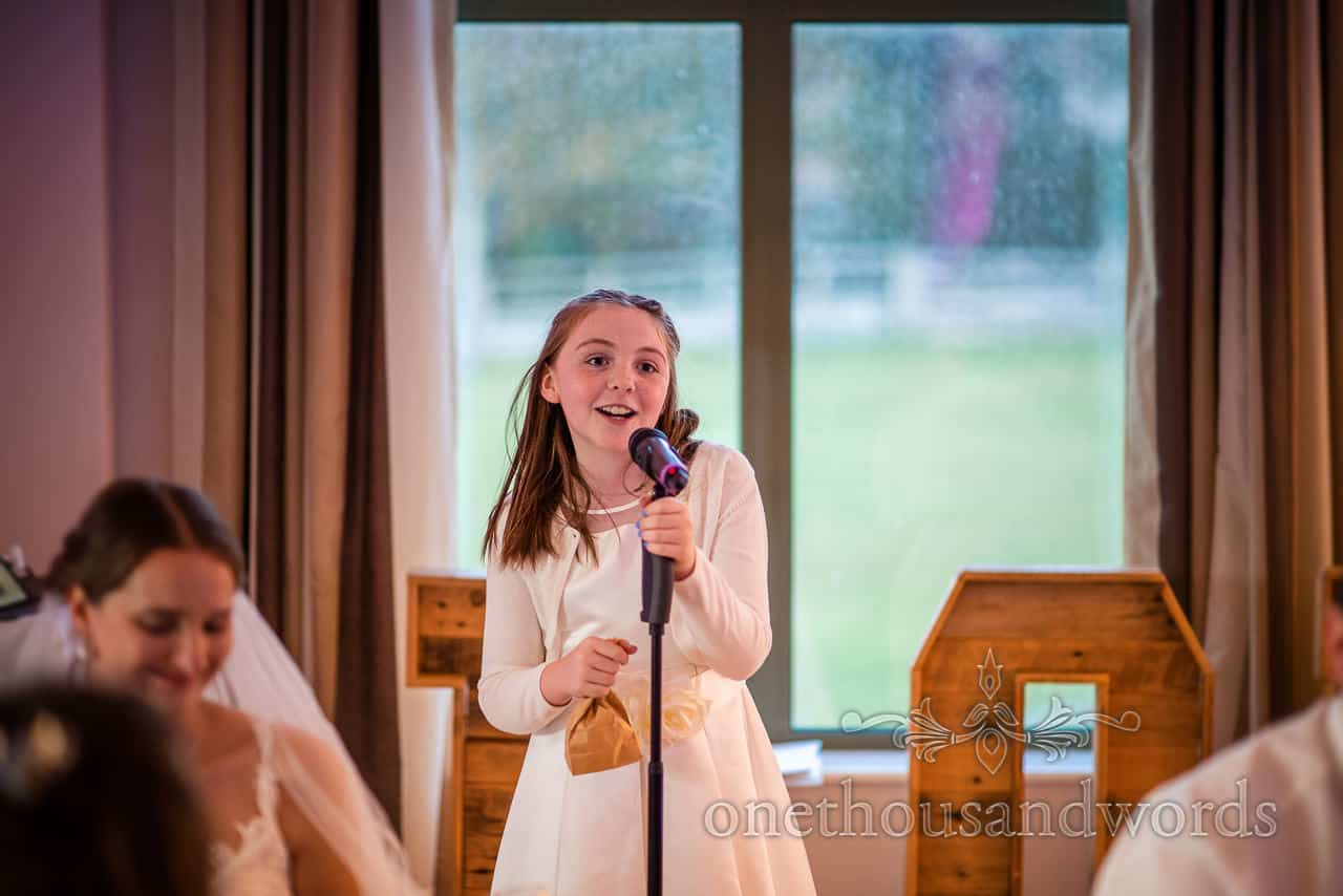 Young flower girl announces wedding quiz with microphone from village hall wedding photographs