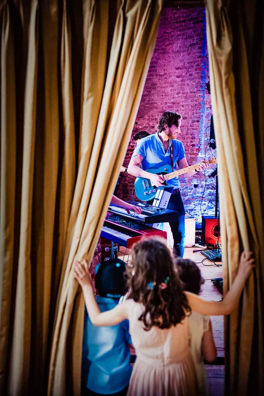 Lulworth Castle Dorset documentary wedding photograph of children wedding guests watching wedding band rehearse under coloured disco lighting through curtains
