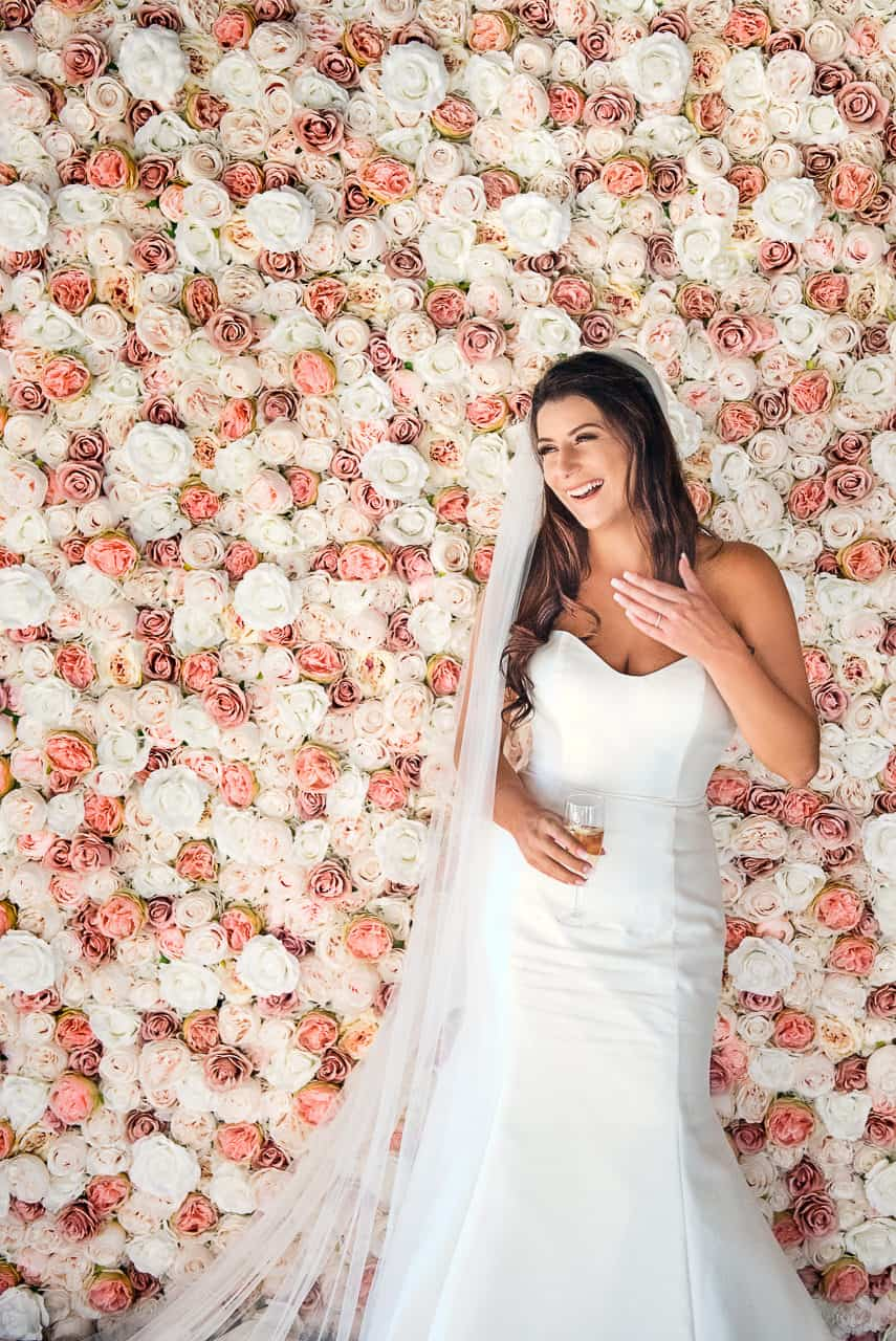 Dorset wedding photographers one thousand words photograph a happy bride in her white wedding dress with a glass of champagne stood against a pink and white rose flower wall