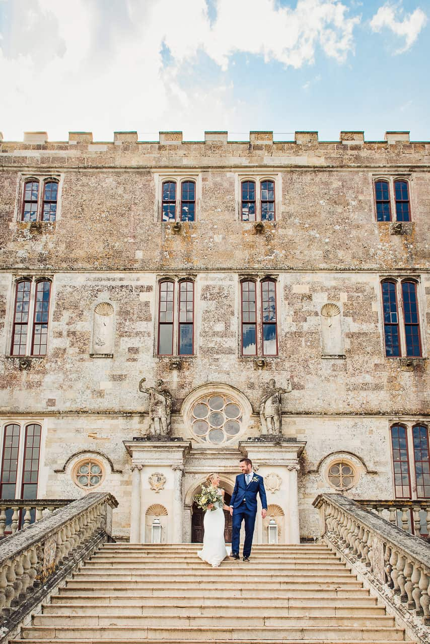 Bride and groom walk hand in hand down stone staircase at Lulworth Castle wedding venue in Dorset countryside photograph by one thousand words