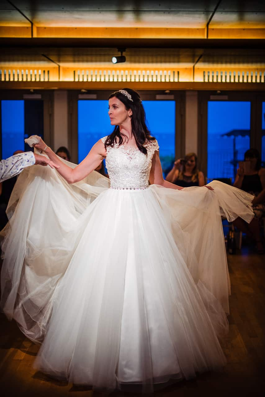 Bride dancing on wedding evening in white wedding dress against blue windows photograph