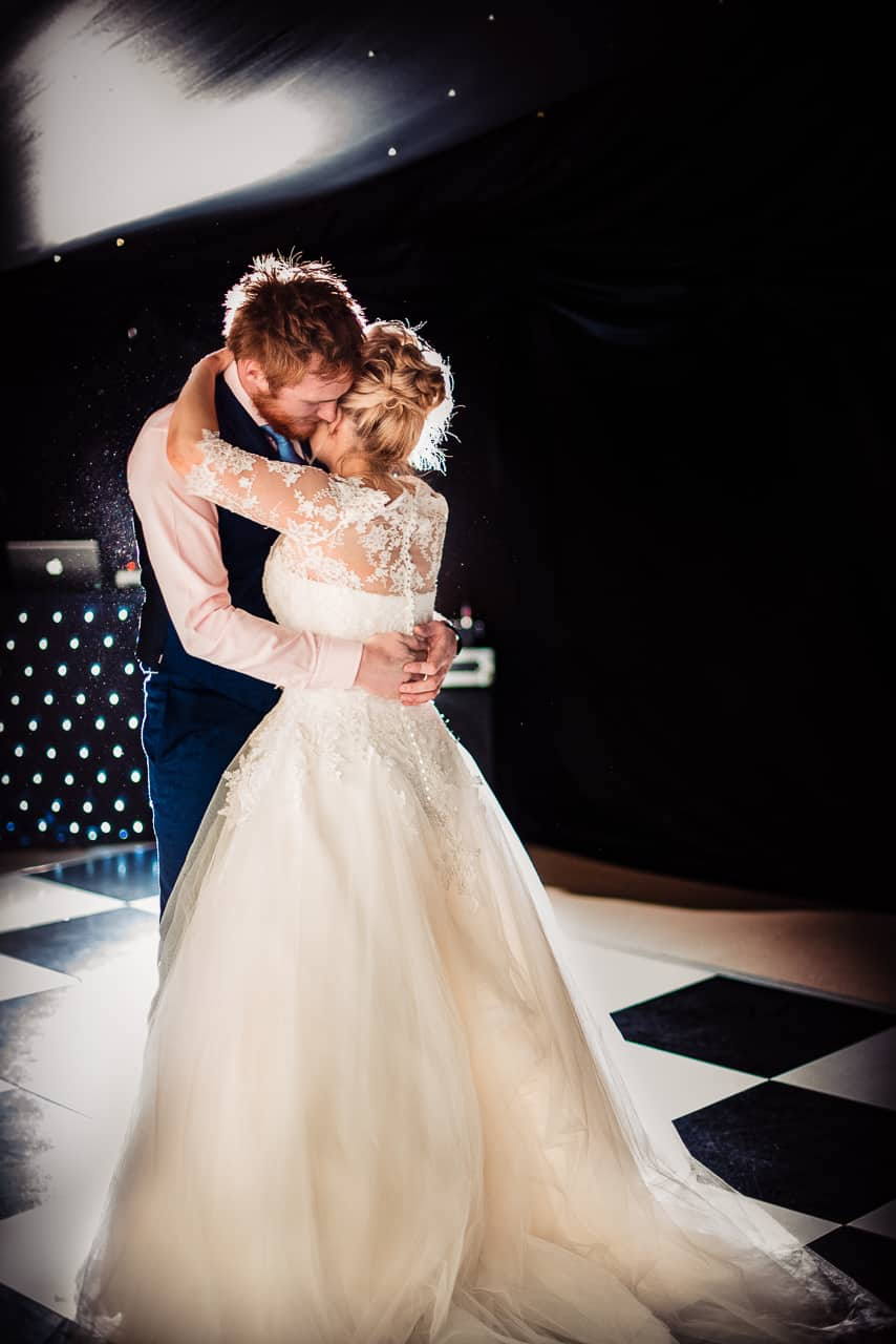 Bride and groom emotional first dance photograph on chequerboard dance floor in black wedding marquee