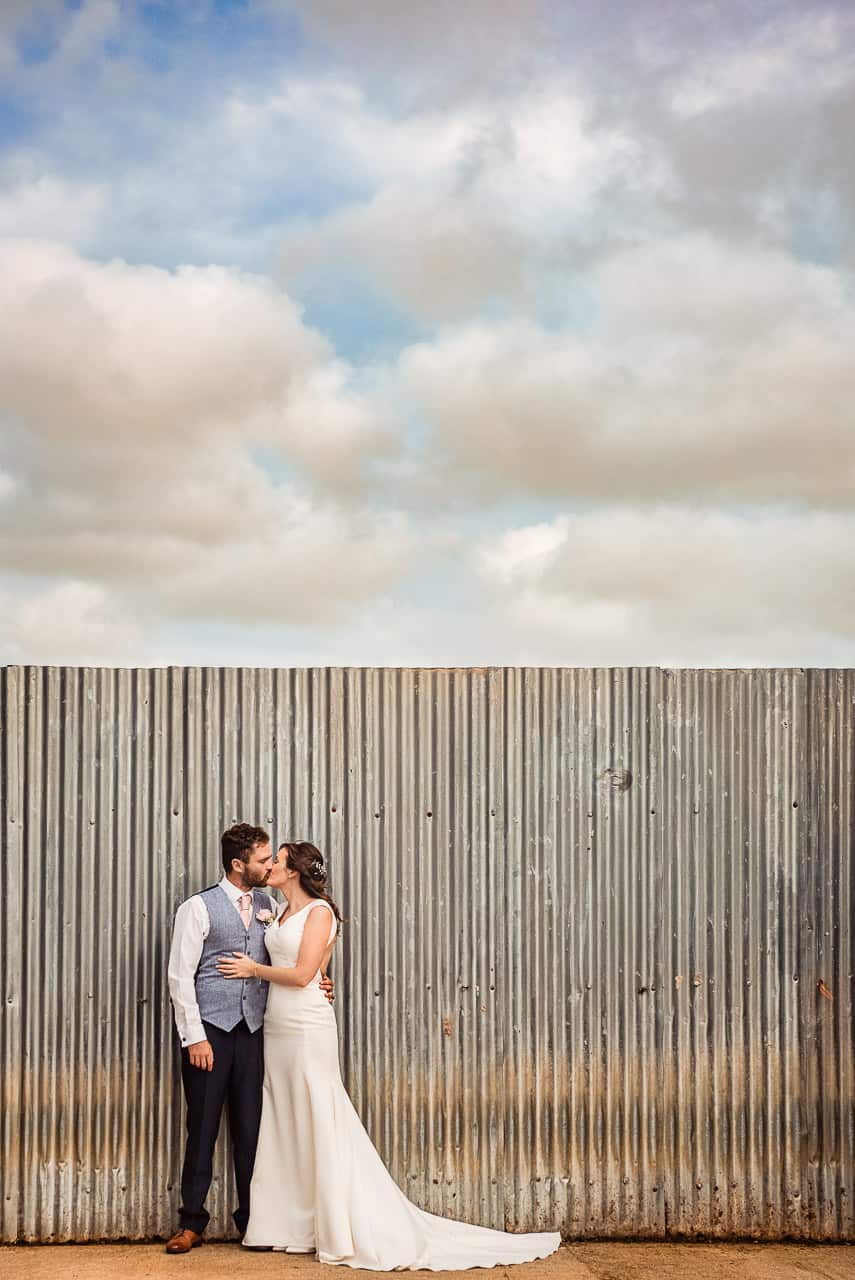 Countryside wedding bride and groom kissing couple photograph with corrugated metal farm wall