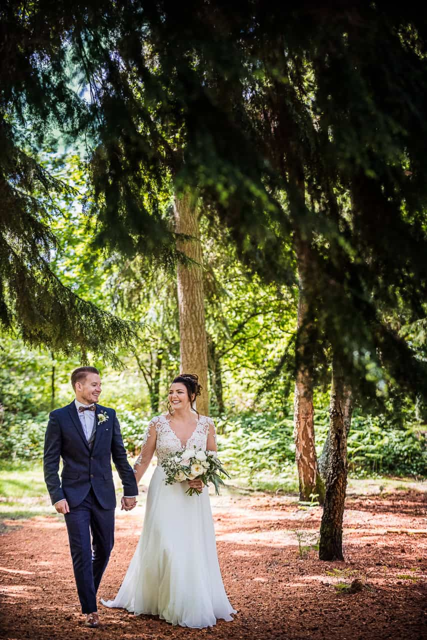 Happy bride and groom walk hand in hand through New Forest woodland Hampshire wedding photograph