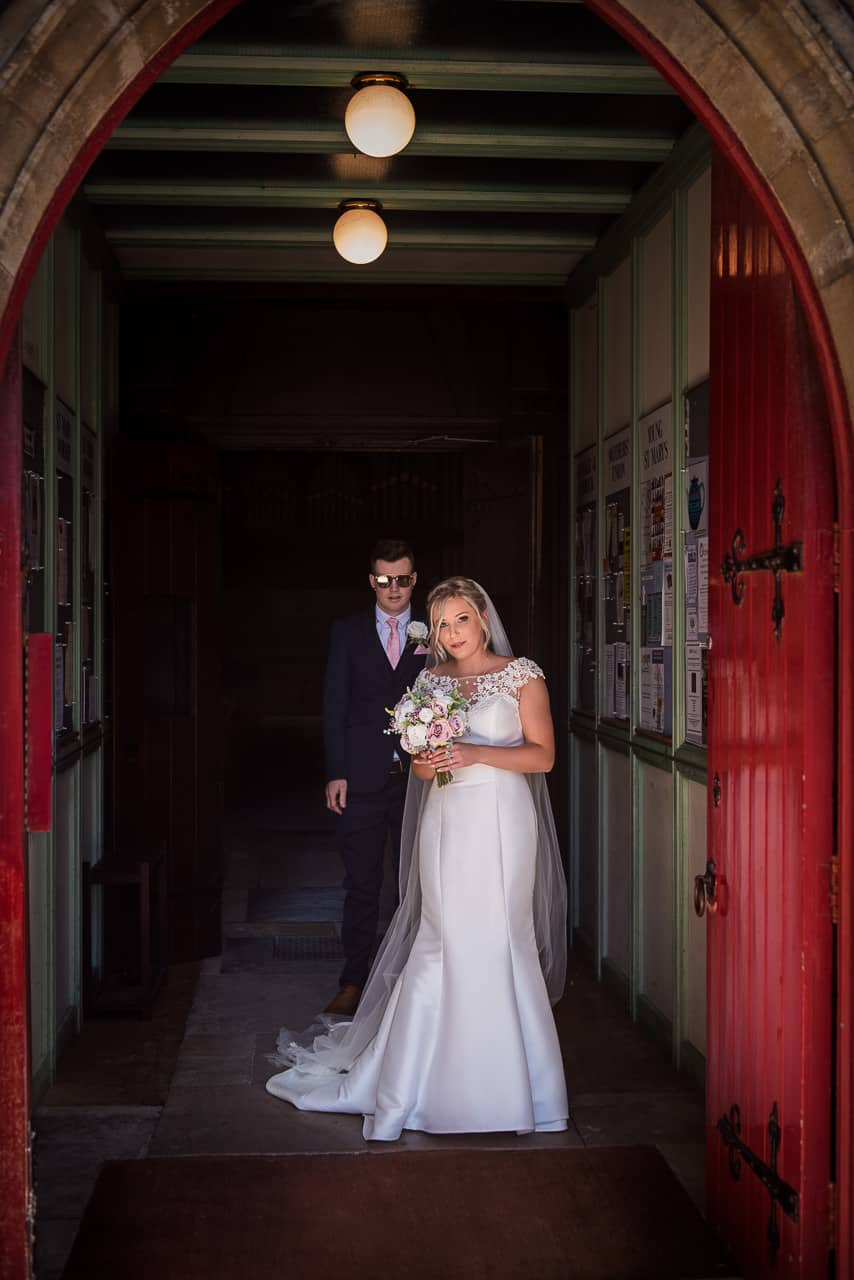 Wedding photography of bride in white wedding dress holding pink flower wedding bouquet with groom in sunglasses waiting to exit red church doorway in Dorset
