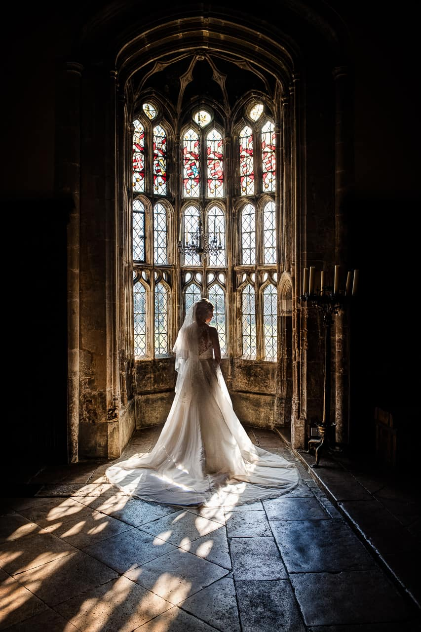 Bride in white wedding dress stands in ancient stone building oriel window at Athelhampton house stately home Dorset wedding venue photograph