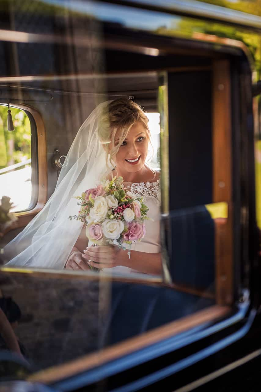Happy smiling beautiful blonde bride portrait photograph in classic wedding car with pink wedding flower bouquet in Dorset