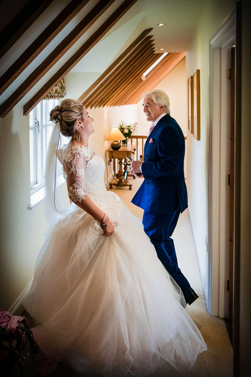Documentary wedding photography of bride in white wedding dress at home on wedding morning laughing with father of bride wearing blue wedding suit photo by one thousand words wedding photographer Dorset