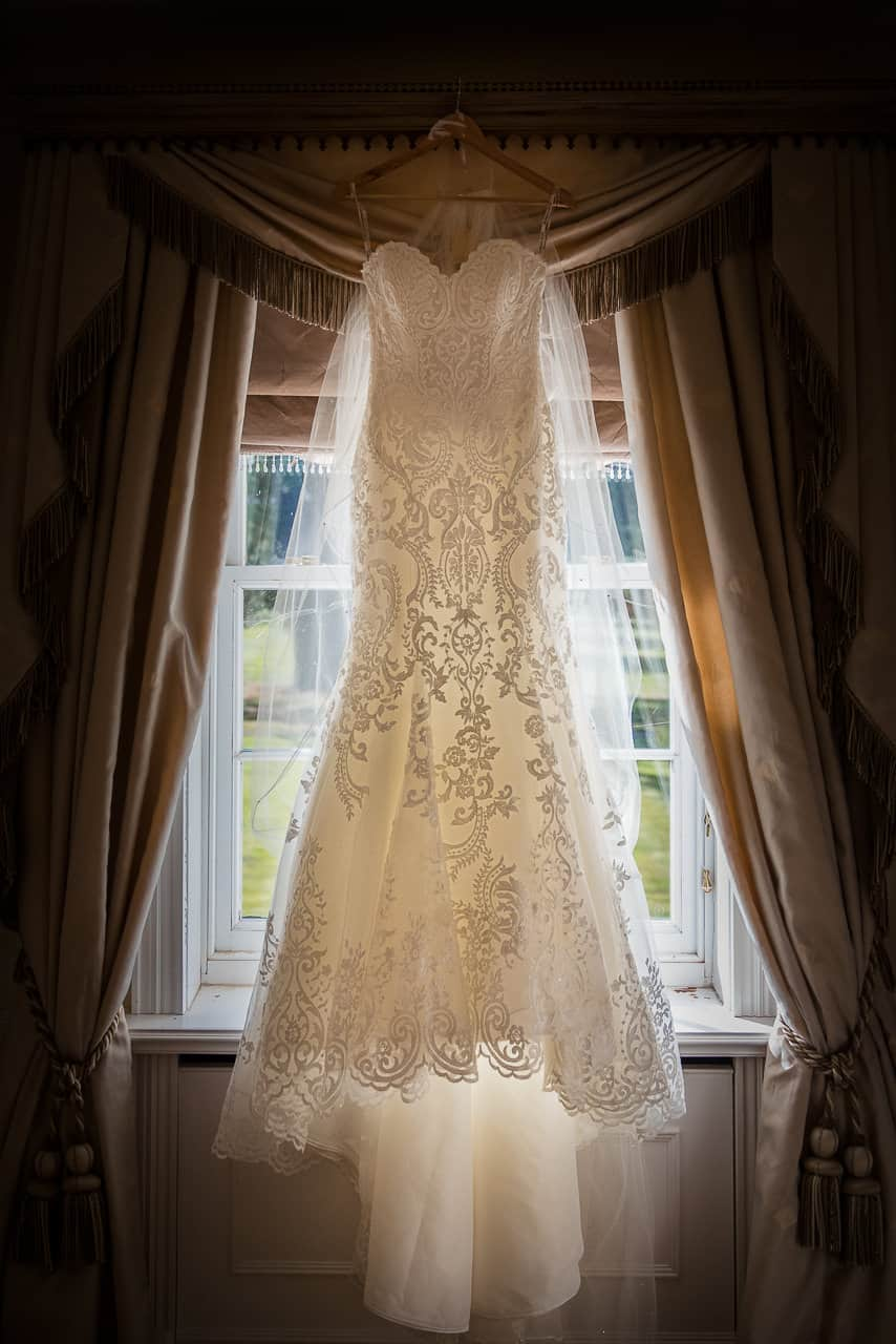 Detailed wedding photograph of glowing white lace detailed a line Maggie Sottero wedding dress and vale hanging in the window at stately home Hethfelton