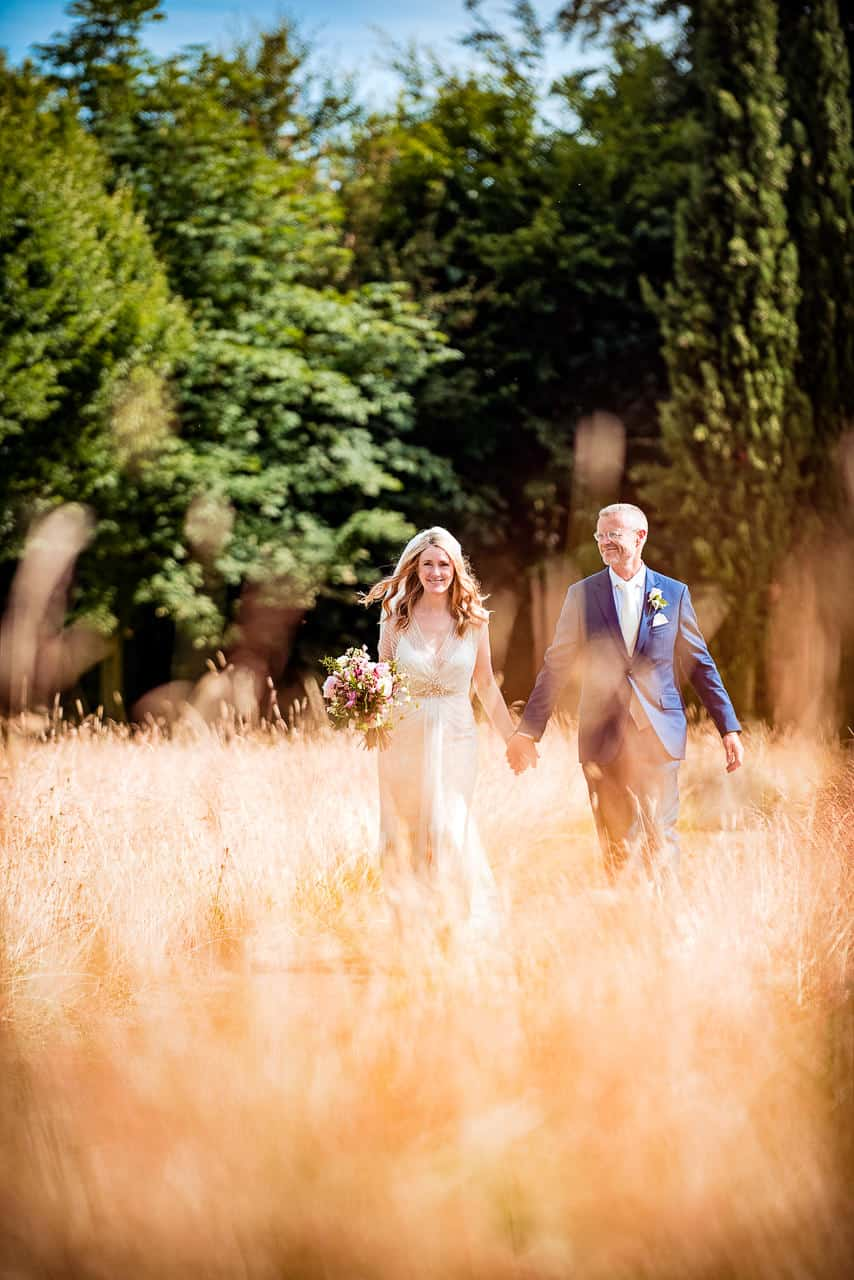 Smiling bride and groom walk through countryside field summer wedding photograph one thousand words photographer in Dorset