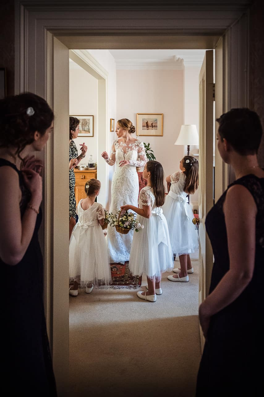 Dorset documentary wedding morning preparation photograph of bridesmaids watching bride and flower girls in white dresses with white flower baskets at home through doorway