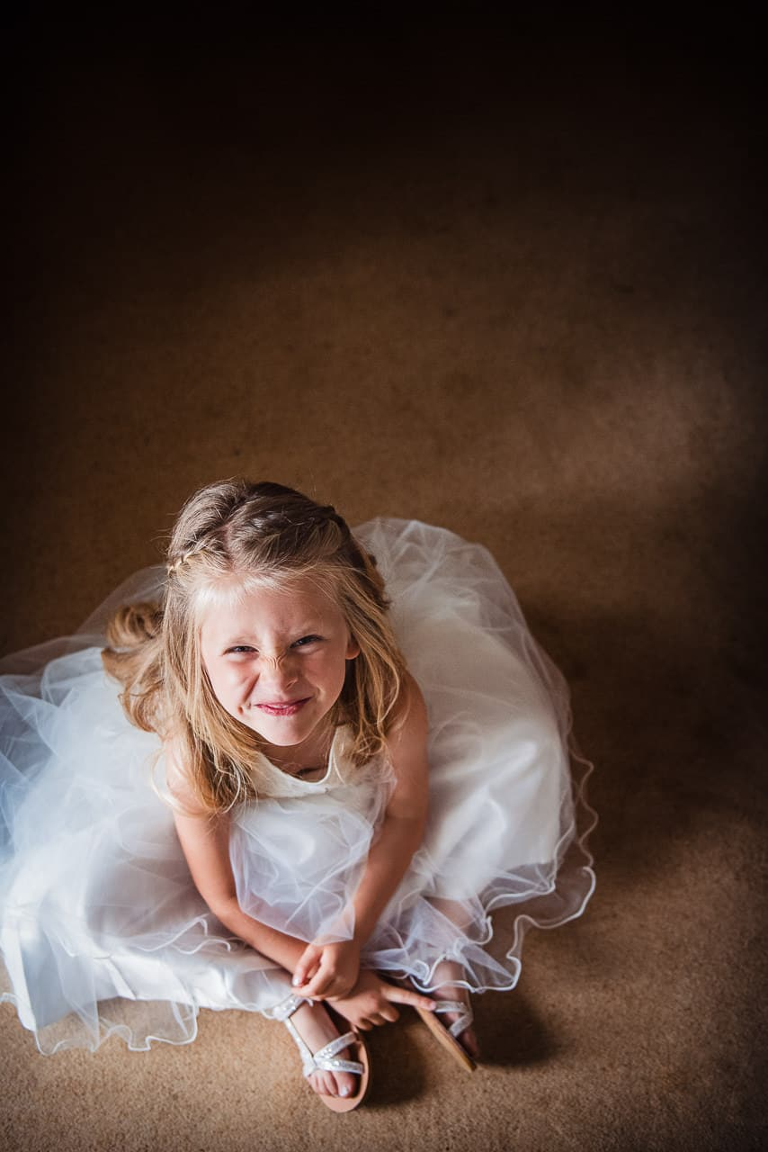 Wedding portrait photograph of cheeky blonde flower girl in white flower girl dress and white diamante sandals by one thousand words Dorset wedding photographer