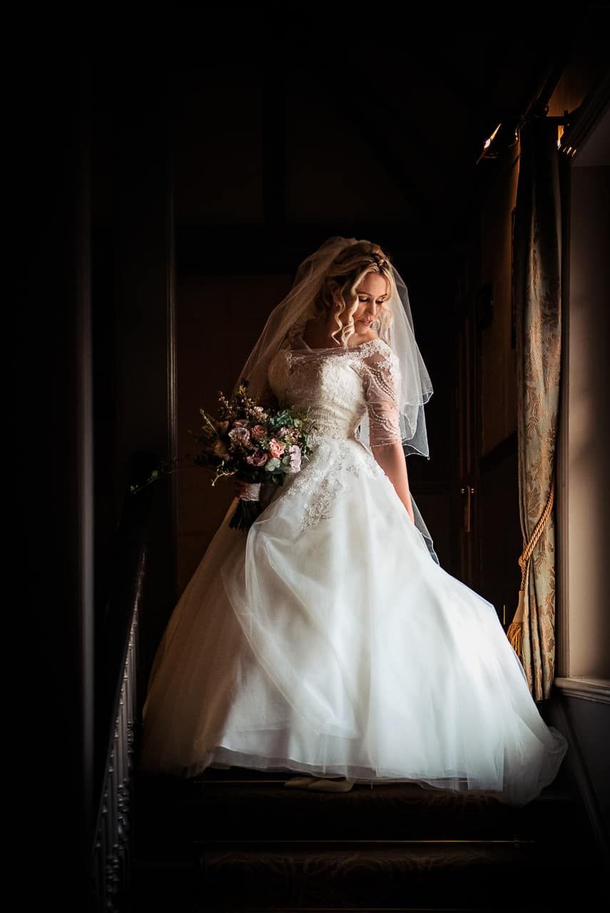 Wedding photograph of beautiful bride in white wedding dress next to window light holding bouquet of wedding flowers