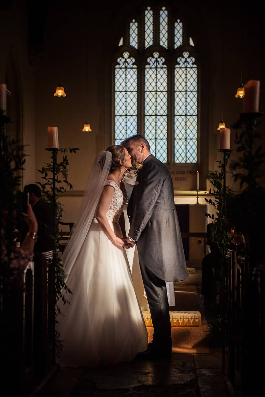 Wedding photograph of a candlelit first kiss between bride and groom at a church wedding ceremony in Dorset