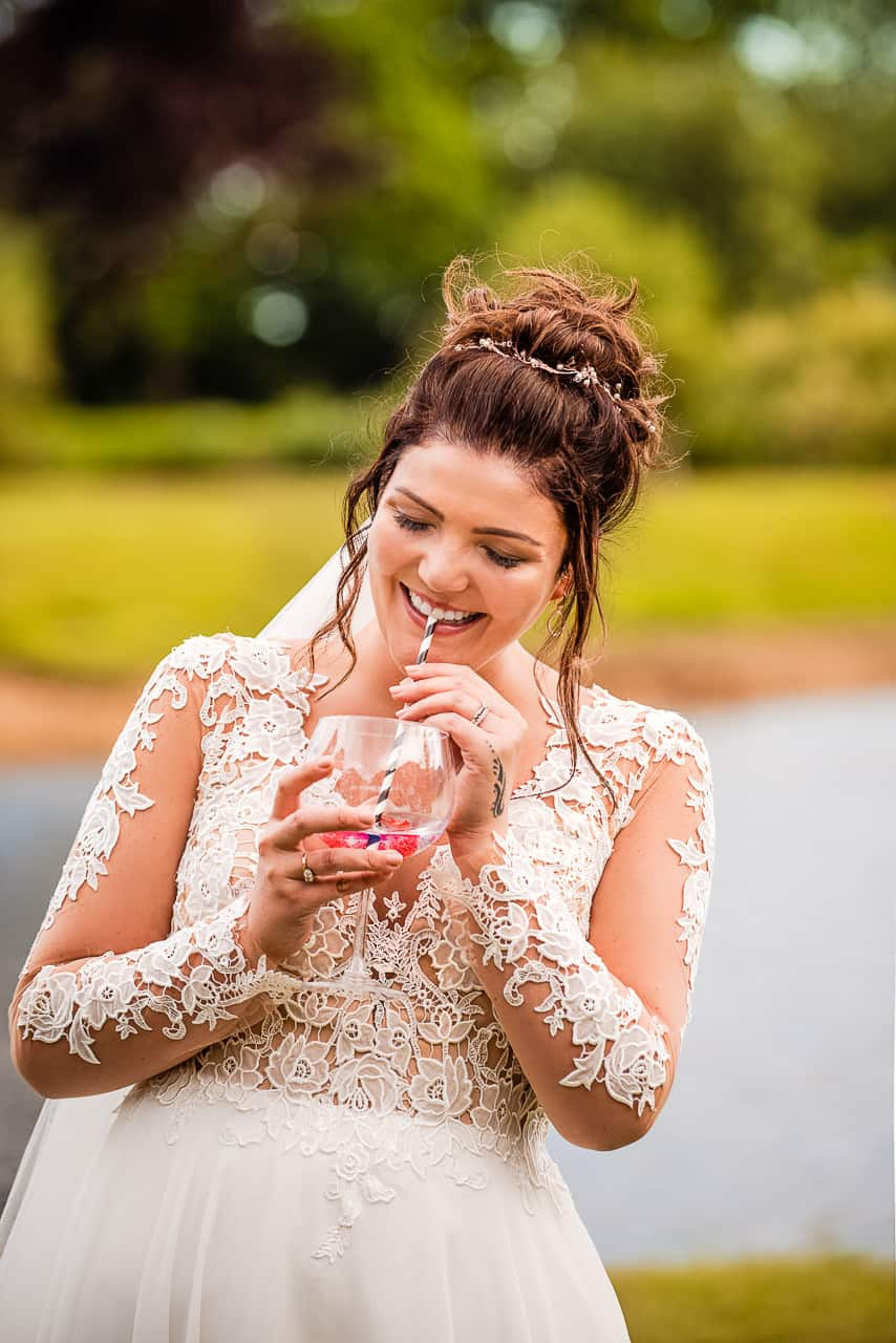 Documentary photo of happy Dorset bride laughing whilst she drinks cocktail