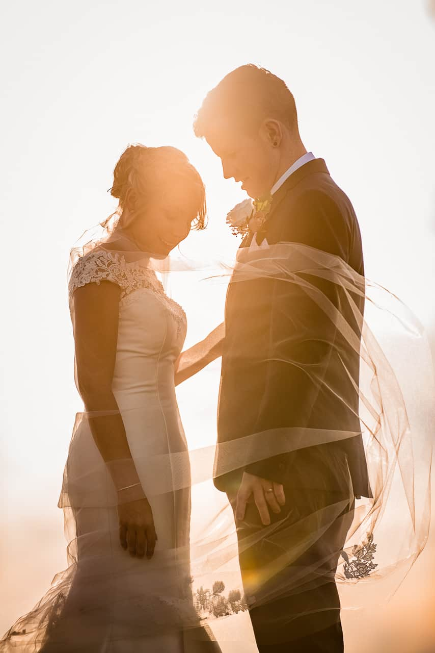 Smiling happy bride and Groom low sun flare silhouette photograph with wedding veil blowing in the wind
