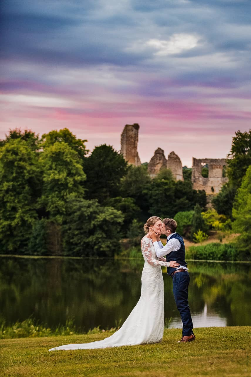 Wedding couple kiss with sunset at countryside lake reflection wedding photo with ruined castle in background at Sherborne Dorset by one thousand words wedding photographer