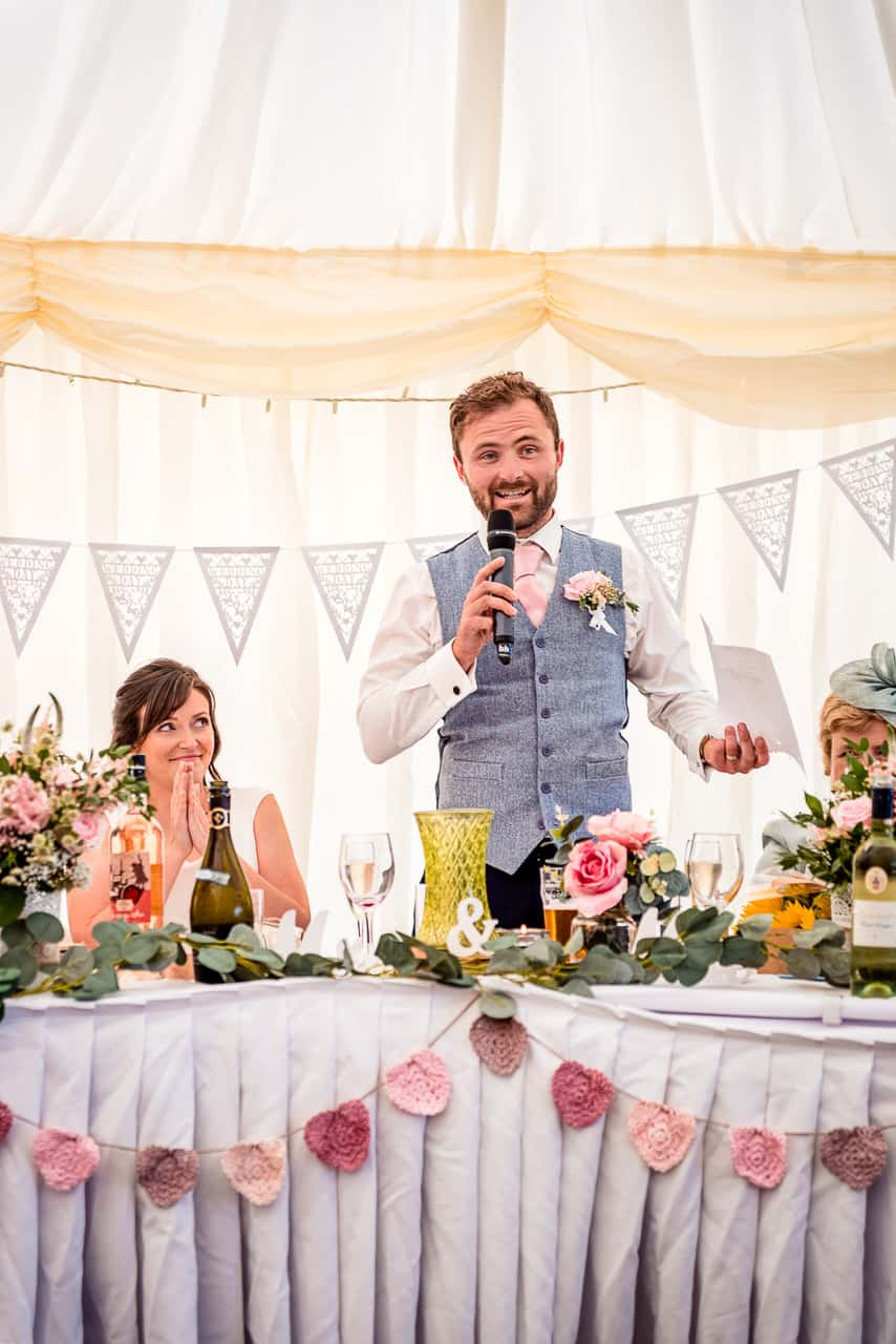 Bride watches and applauds new husband in blue tweed waistcoat as he makes his grooms speech at top table in countryside wedding marquee with pink flowers photo by one thousand words