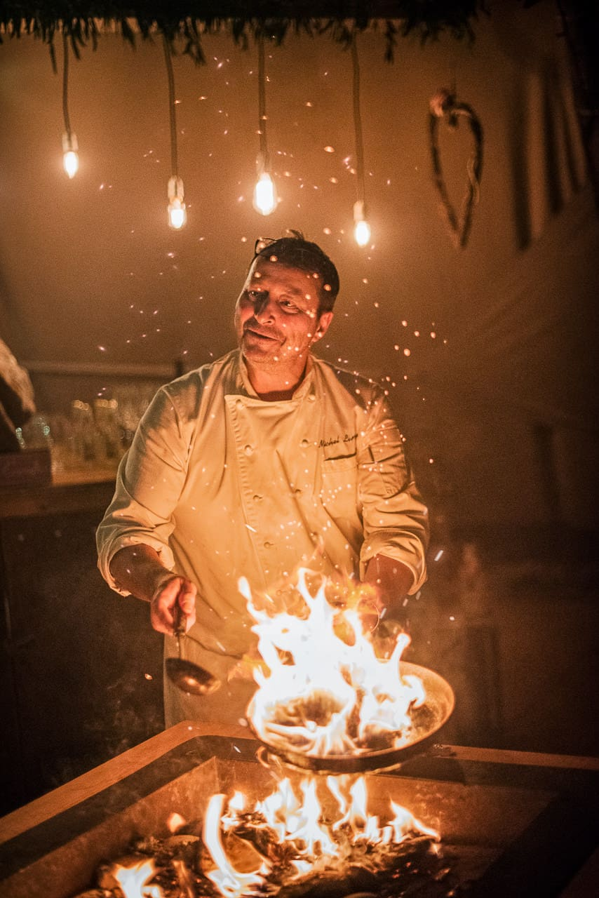 Documentary wedding photograph of wedding catering chef in his whites cooking over an open fire with Sparks inside wedding tipi