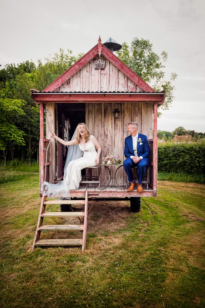 Laughing bride and groom in blue wedding suit in old retro chic wooden caravan from countryside wedding photographs