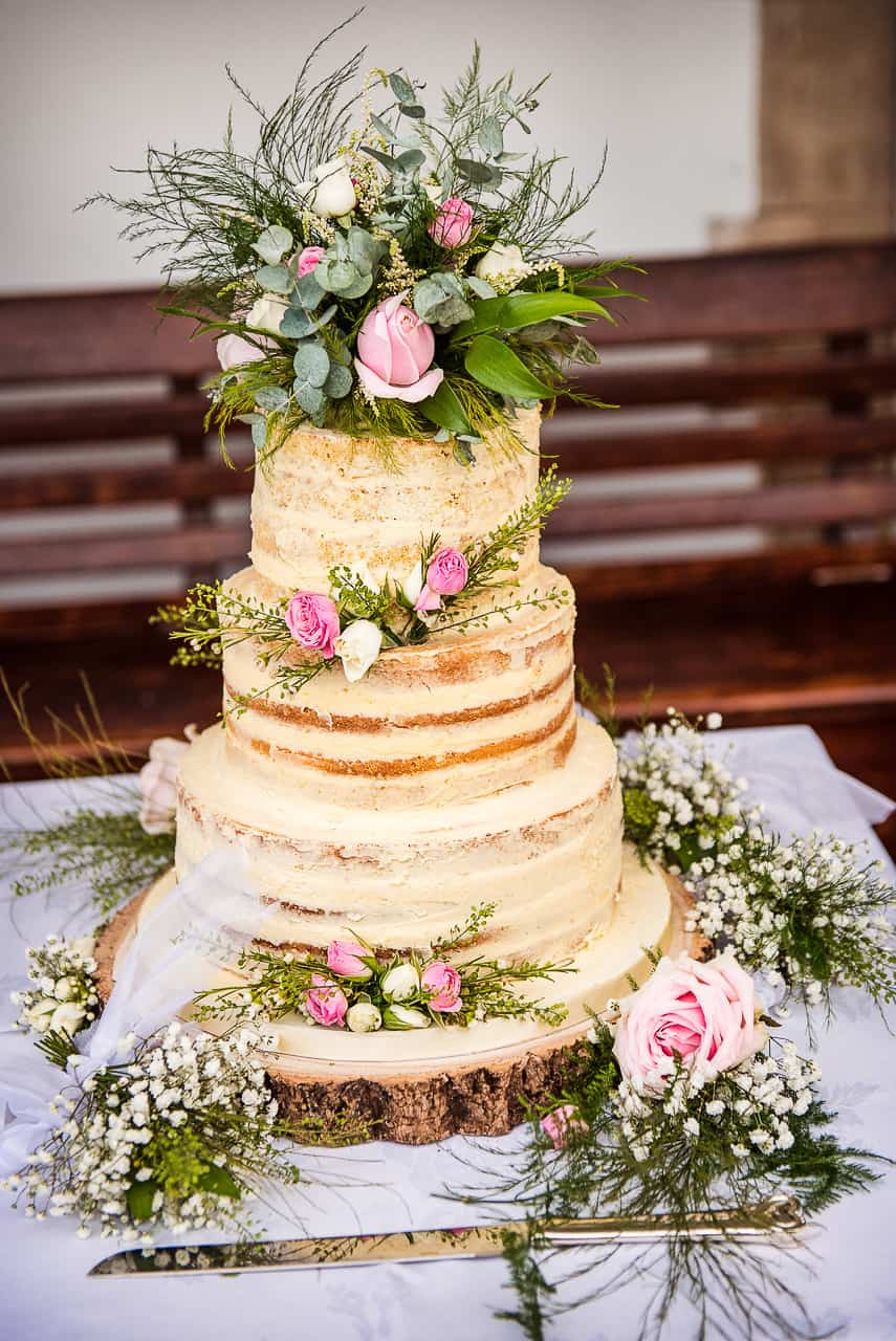 Photograph of three-tier naked wedding cake decorated with green foliage and pink flowers on log slice with cake knife