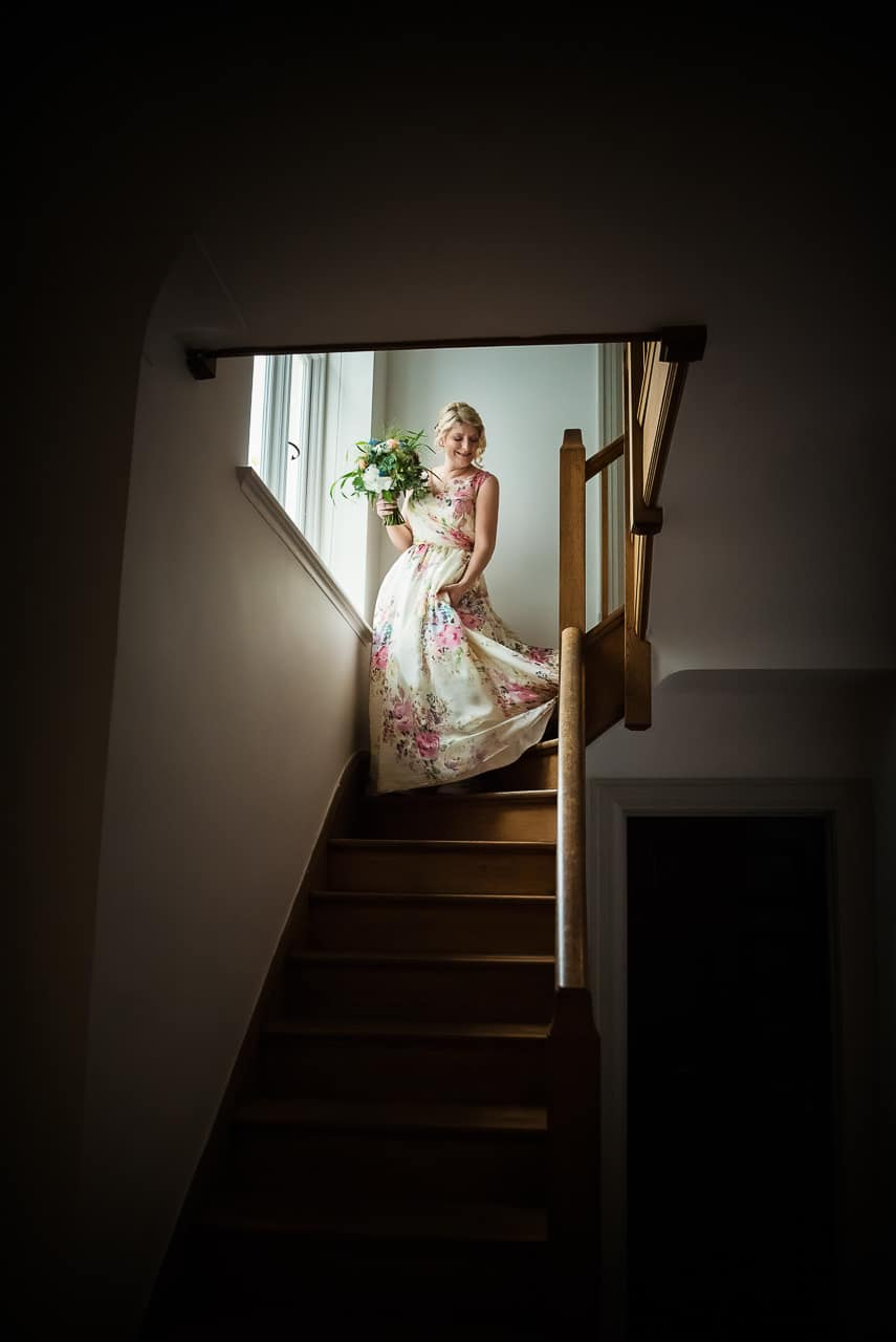 Bride in printed floral wedding dress holding bouquet descending staircase from documentary wedding photographs on Dorset wedding morning