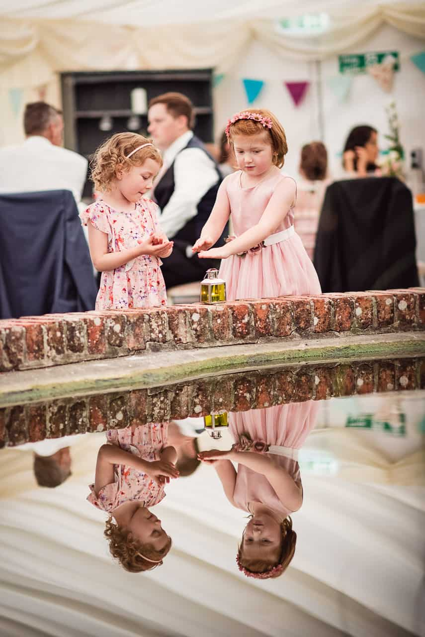 Cute flower girls in pink dresses photographed playing with wedding candle decorations reflected in marquee wedding water feature photograph