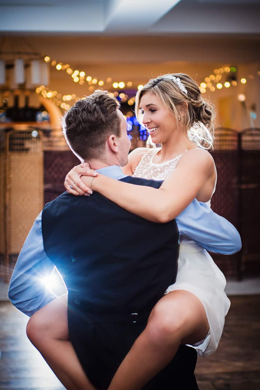 Groom in navy waistcoat lifts smiling beautiful bride during backlit first dance routine at wedding evening reception photographs