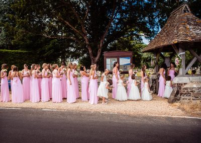 Documentary wedding photo of 28 bridesmaids in pink dresses wait outside Dorset church wedding ceremony