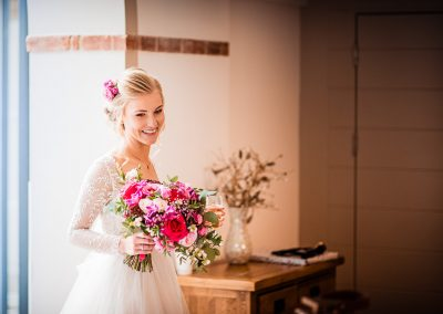 Beautiful smiling bride with pink and red wedding bouquet enters Italian Villa Wedding venue in Dorset