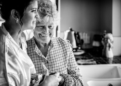 Black and white documentary wedding photo of bride and grandmother hugging on Dorset wedding morning