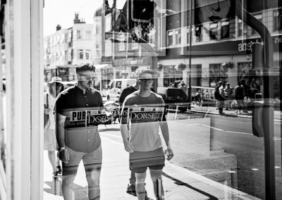 Black and white urban documentary wedding photo of groomsmen walking through Swanage Town on wedding morning in Dorset