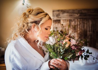 Beautiful blonde bride smells wedding bouquet documentary wedding photo by one thousand words