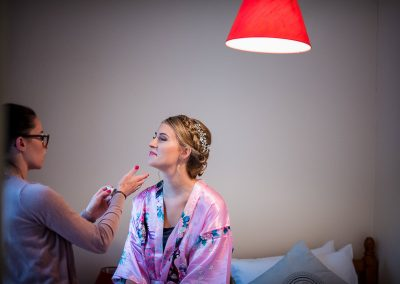 Documentary weddin gphotograph of bridal make up being applied under red lamp shade