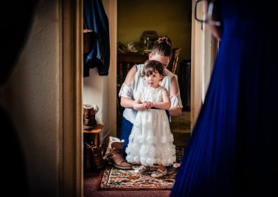 Bridal preparation photograph of flower girl being buttoned into her dress