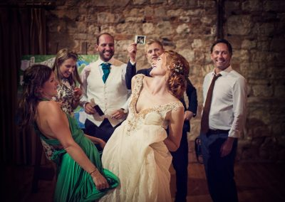 Bride and bridesmaid dancing at Lulworth Castle as groomsmen shake polaroid wedding photos