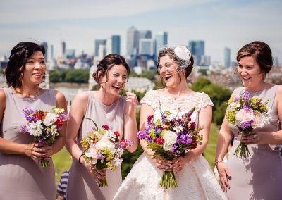 Bride and bridesmaid photographed as they laugh in Greenwich park with London city in the background