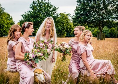 Bride and bridesmaids in pink dresses laughing in countryside field sat on sheep photo by one thousand words