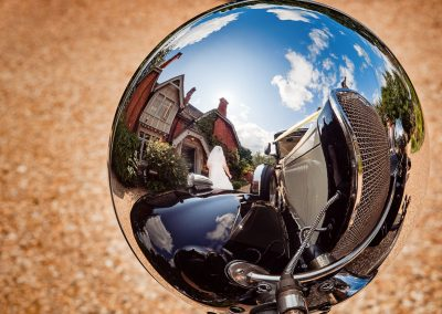 Bride and Old Vicarage wedding venue reflected in chrome light of lcassic wedding car photo by one thousand words wedding photographers