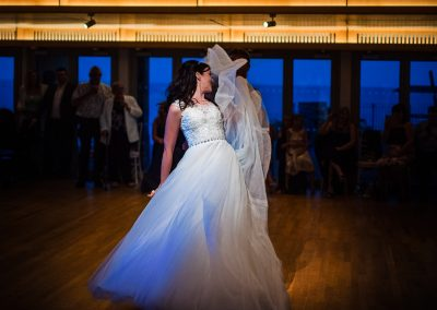 Bride flicks wedding dress during first dance routine under a spotlight on the dancefloor with blue windows