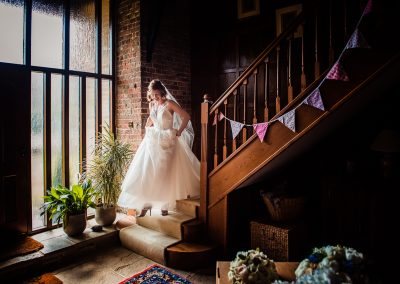 Bride in white wedding dress descends wooden staircase with bunting at home on wedding morning