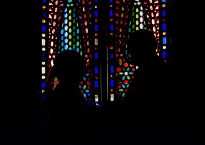 Bride and groom silhouettes against stained glass windows at Alhambra room in Rhinefield House Hotel New Forest wedding venue