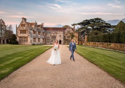 Laughing bride and groom outside Athelhampton House wedding venue in Dorset photo by one thousand words wedding photographers
