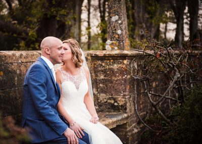 Bride kisses groom on cheek on stone seat at Athelhampton House wedding venue