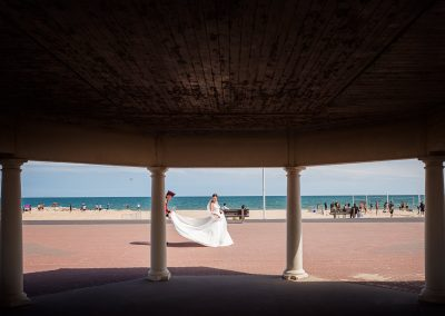 Military groom fans our brides white wedding dress at Sandbanks beach pavilion at Dorset seaside