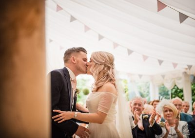 Parley manor first kiss wedding photograph as guests applaud by one thousand words