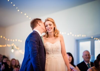 Groom kisses happy bride in wedding ceremony photograph at Kings Arms Pavilion in Dorset