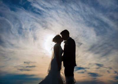 Bride and groom wedding photo kissing in silhouette against cloudy sky photo by one thousand words wedding photographers in Dorset