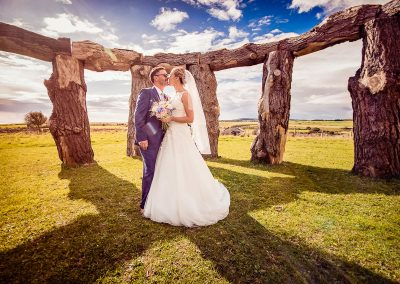 Wedding couple kiss on summers day at wood henge in Dorset